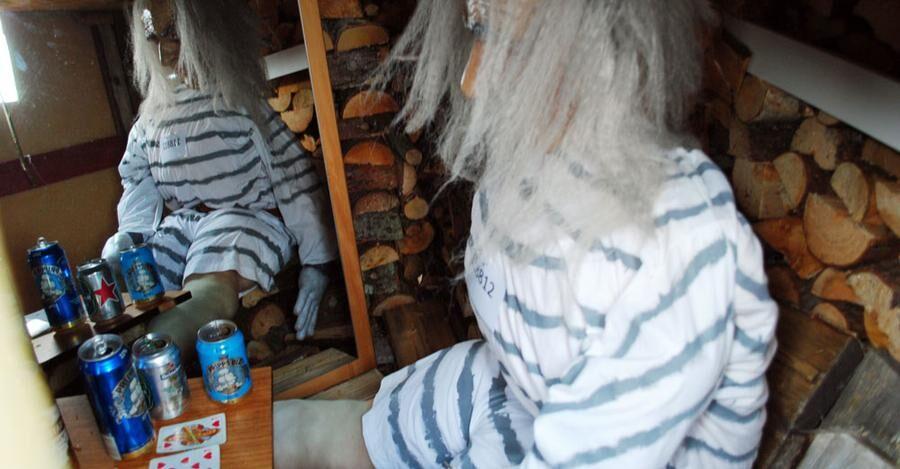 Öppnar man en lucka kan se hur den äldste internen har det. Han spelar kort omgiven av tomma ölburkar.