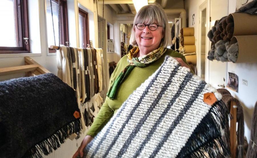 """""""Den här är skön att ha på kalla golv."""" Marianne Fröberg visar upp en ullmatta som är vävd i spinneriets vävstuga. Mattorna görs av volontärer och säljs i den egna butiken."""