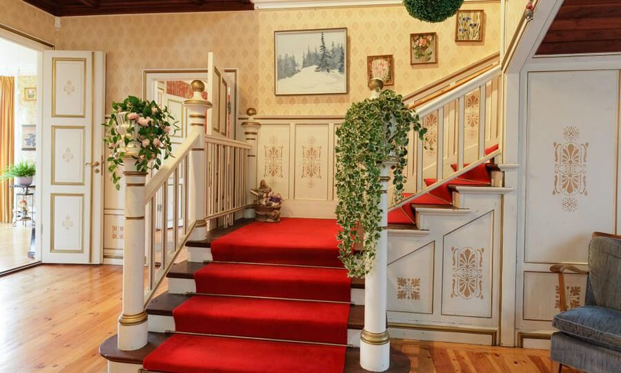 Det är högt i tak i hallen och trappan är klädd i röd matta.