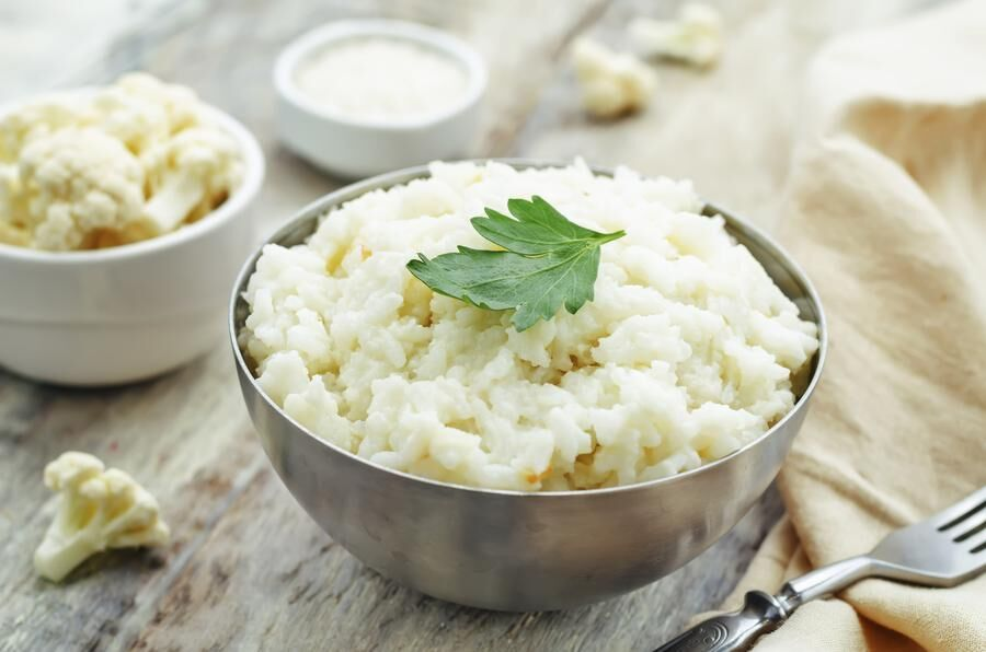 creamy cauliflower garlic rice on a white wood background. the toning. selective focus