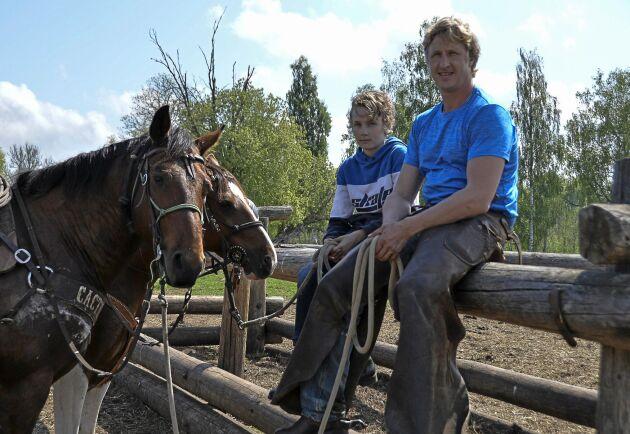 Far och son pustar ut efter en lång svettig förmiddag i hagen för både människor och hästar.