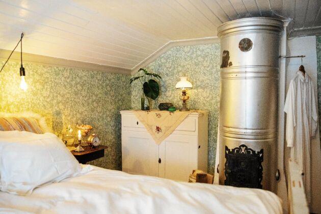 Mönstrade, gammeldags tapeter även i sovrummet med sin tidstypiska metallmålade kakelugn.