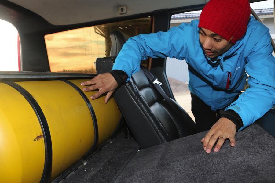 Martin visar den säkra gastanken bakom ryggstödet i baksätet.