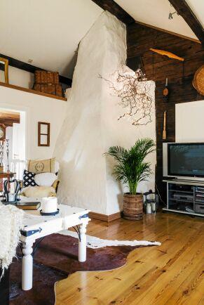 Övervåningen får rymd av att taket är öppet ända upp till nock och med den vitmålade murstocken i centrum.