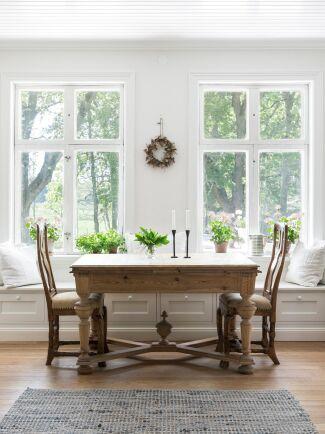 Matrummet som går i fil med köket med fin känsla från förra sekelskiftet. Under fönstren finns en platsbyggd soffa som rymmer många runt bordet och även är en förvaringsplats.
