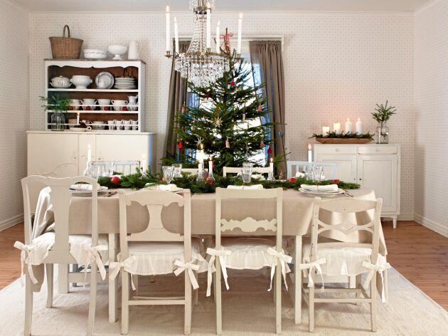Ljust och välkomnande. Sandra och Adam har dukat upp ett vackert julbord med levande ljus, lingonris och grankvistar.