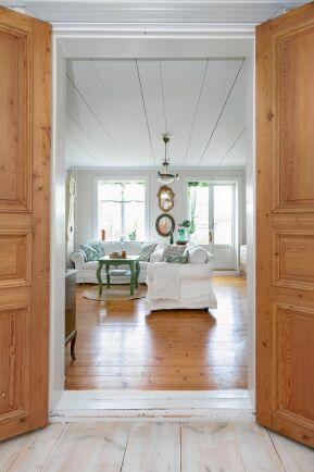 Breda golvplank och vitmålat tak i den luftiga salen.
