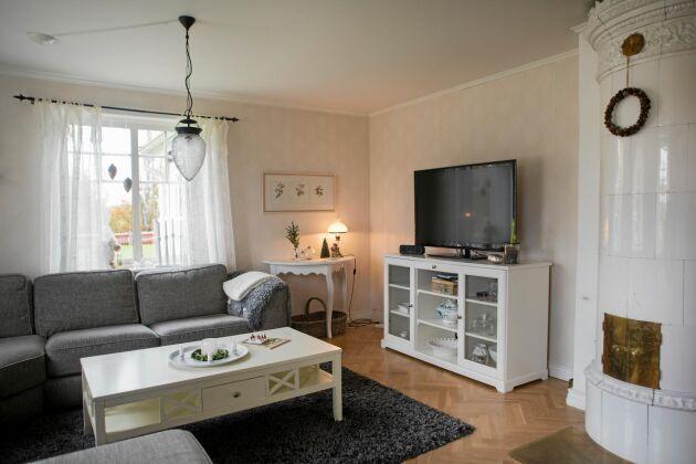 Vilsamma färger i vitt och grått i vardagsrumner med fin kakelugn.
