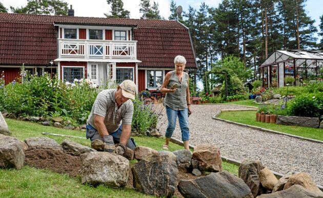 Uffe och Sivan använder sig mycket av de stenar som redan finns på och i anslutning till trädgården. Här håller de på att anlägga en ny rosenrabatt.