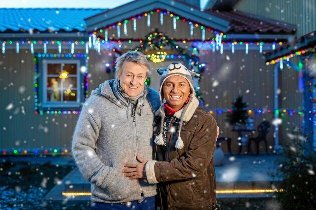 """Lars Lerin med sin make Manoel """"Junior"""" Marques framför deras julupplysta hus."""