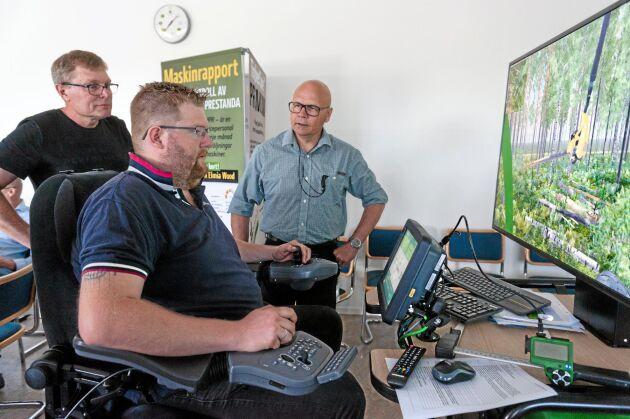 När John Deere ordnar simulatorträff är både skolor och företag inbjudna. Joakim Söderberg, utbildningsansvarig på Skogstekniska testar att köra skördare, medan Thomas Åström, metodutbildare på John Deere, (i rutig skjorta) ger tips.