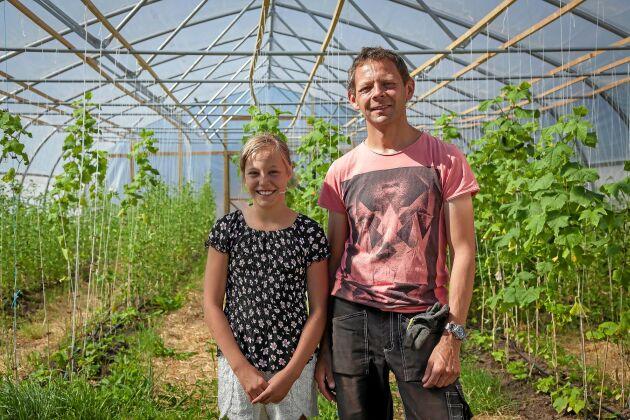 Ebba och pappa i Mikael inne i det nya växthuset där gurka och tomater växer så det knakar.