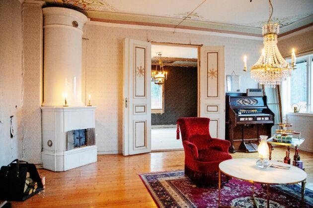Den stora salen har en pampig takmålning och kakelugn. Möblerna i gammeldags stil har de köpt på loppis och auktion.