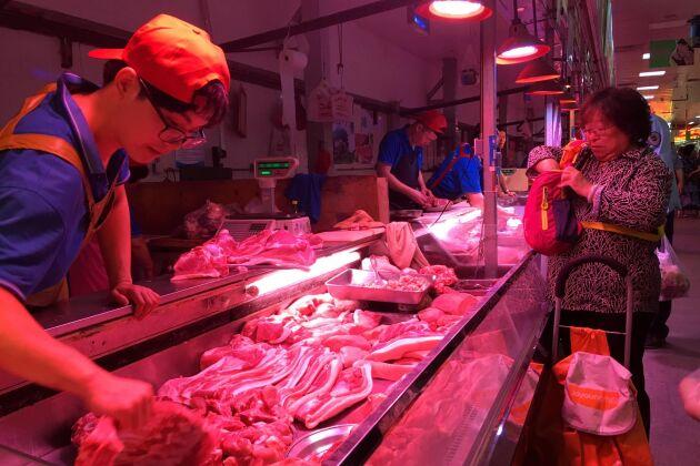 Nu är inte bara priserna höga, det även svårt att få tag i något kött alls. På bilden en köttförsäljare på en marknad i Peking i September.