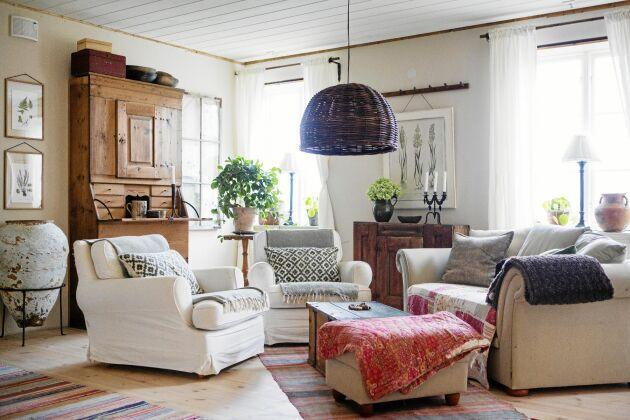Vardagsrummet med milda naturfärger och mycket grönt är en blandning av gammalt och nytt.