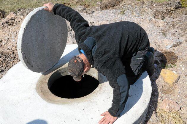 Jörgen Olsson, en av Ölands många lantbrukare som drabbats av torkan, lyfter på det tunga cementlocket och tittar ner på vattenspegeln i den nya brunnen.