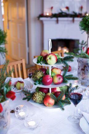 Ett fruktfat med röda juläpplen och granris och får inta en hedersplats på matbordet.