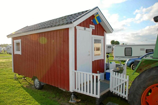 Det röda lilla trähuset är campingens enda verkliga husvagn med staket och blomlådor.