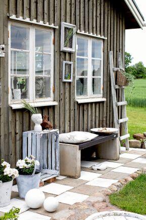 Trine kan konsten att förvandla en enkel husvägg till ett riktigt blickfång. Med en mix av gamla betongplattor, kullersten och fina loppisfynd skapas stämning i vitt och gråton.