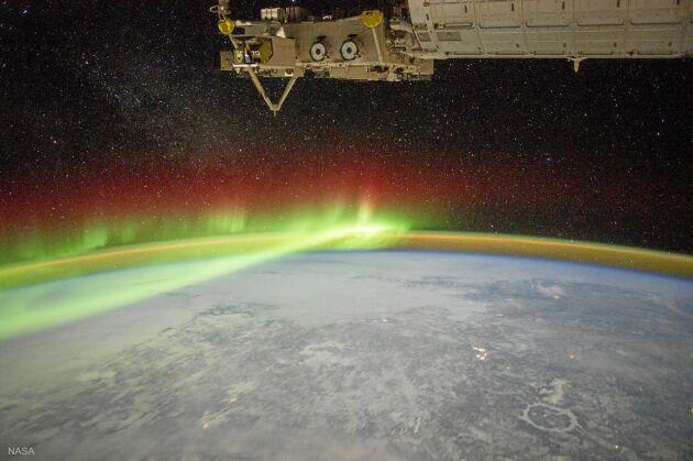"""Från boken: Polarsken (på norra jordklotet även kallat norrsken) sett från rymdstationen ISS över Kanada. På bilden ses också """"luftsken"""", ett svagt grönblått sken fördelat över atmosfären."""