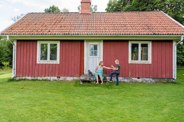 Anja och Anton framför den lilla stugan som är en av de få gamla byggnader som gick att bevara.