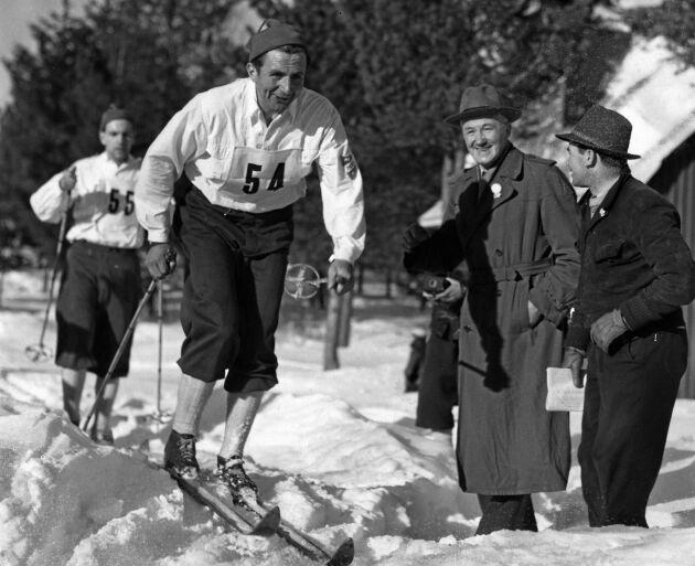 """Nils """"Mora-Nisse"""" Karlsson vann Vasaloppet nio gånger. Här skidar han leende förbi pappa Viktor Karlsson vid Mångsbodarna år 1950 där """"Mora-Nisse"""" segrar på tiden 6.08.25."""