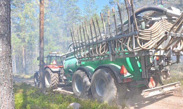 Lantbrukare fraktar vatten till släckning av skogsbrand.