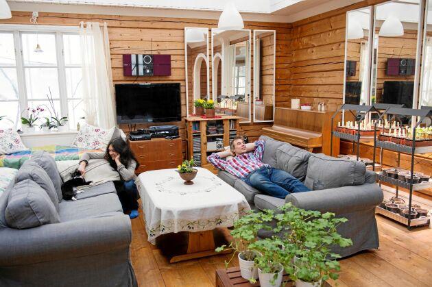 Rosmary och Anders njuter av ljuset och värmen i vardagsrummet inne i timmerhuset. Här står värmekrävande sticklingar och plantor och väntar på att flytta ut till växthuset lite senare i vår.