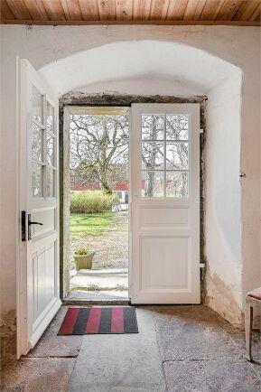 Stengolv och ett vackert valv över entrén i hallen där ytterdörren har försetts med glas och spröjs.