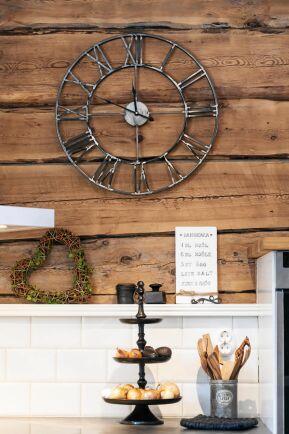 Den stora klockan i gjutjärn och den vita inredningen är fina mot träet i timmerväggarna..