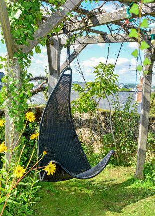 En grånad pergola med en modern stol att hänga i. Ett stilbrottet som blir ett blickfång.