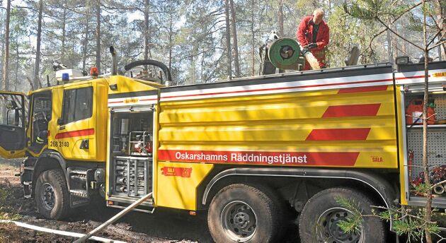 Vattnet som Patrik Andersson hämtat i Ishultssjön fylls på i räddningstjänstens släckningsfordon.