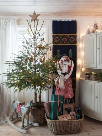 Vem har sagt att grenarna behöver gå ända ner till marken? En fin variant på julgran som spar plats. Här vackert pyntad med små klockor och stjärnor i naturnära färger.