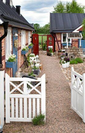 Gammaldags grindar bjuder in besökarna till gårdsplanen framför husets entré. Grinden är nytillverkad och beställd hos en snickare, men passar fint in i gårdsbilden.