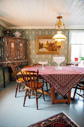 Salens gammeldags inredning med antikt skåp, rejält slagbord och gröna, mönstrade tapeter i 1800-talsstil.