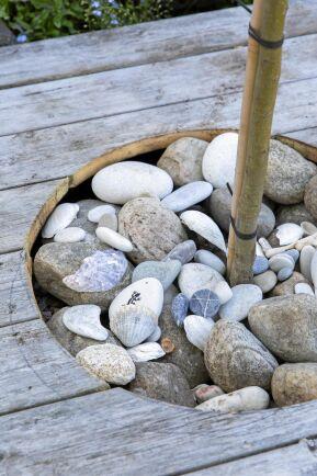 Välslipade stenar och snäckor mjukar upp altandäcket. Att ta upp hål för träd och andra planteringar bryter monotonin på ett stort trädäck.