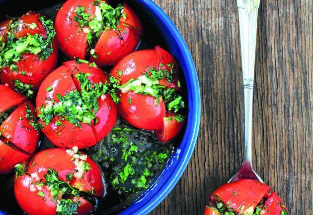 Tomaterna fylls med persilja, dill, koriander, pressad vitlök och olja.