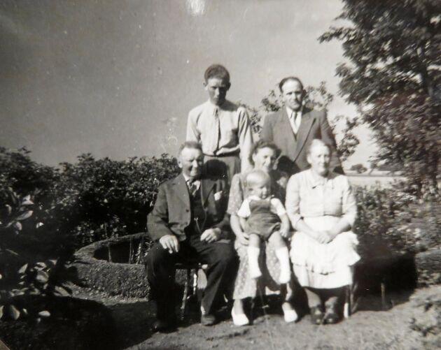Högtidlig familjebild i trädgården, ca 1950, med Thomas far som lång gänglig yngling ståendes t.v.