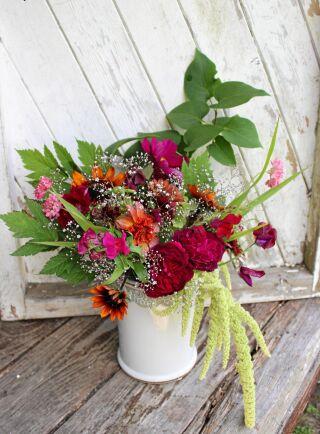 """Ett av Fridas många arrangemang. """"Buketterna ser alltid olika ut beroende på vilka sorter som blommar"""". På bilden: rosor, lejongap, rudbeckia, rosenskära, luktärta, vädd, brudslöja, borstnejlika, amaranth, syrenbuske, dahlia, musselsyska och prydnadsgräs."""