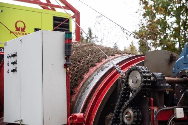 Själva sorteringen sker i den stora perforerade trumman som roterar. Den släpper tillbaka gruset på vägen, medan grästuvor och annat åker ut igen.