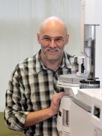 Göran Birgersson bredvid det analysinstrument, en kombinerad gaskromatograf och masspektrometer, som ska användas för att identifiera dofterna som lockar styltflugorna till de träd som angripits av barkborrar.