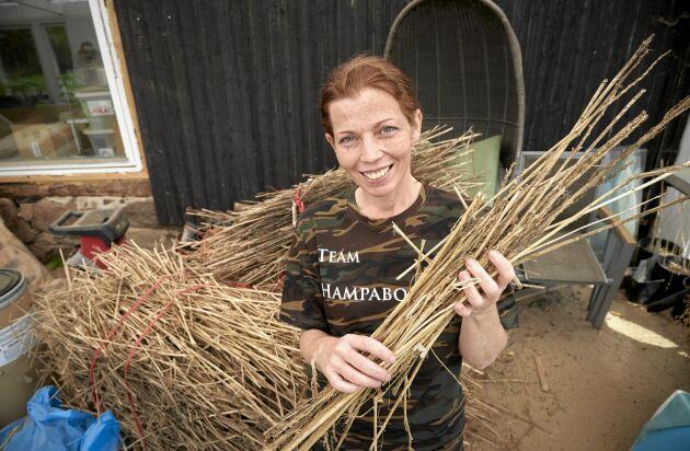 Jeanette visar upp fjolårets skörd, som torkats och rötats och används till isolering och byggmaterial.