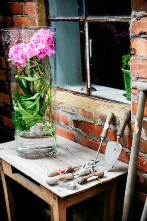 Intill den vackra pionen ligger handsmidda trädgårdsverktyg som Maria säljer i sin butik.