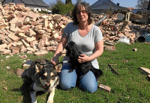 Katarina Hallberg med hundarna Tequila och Chip framför tegelhögen som var hennes hus.