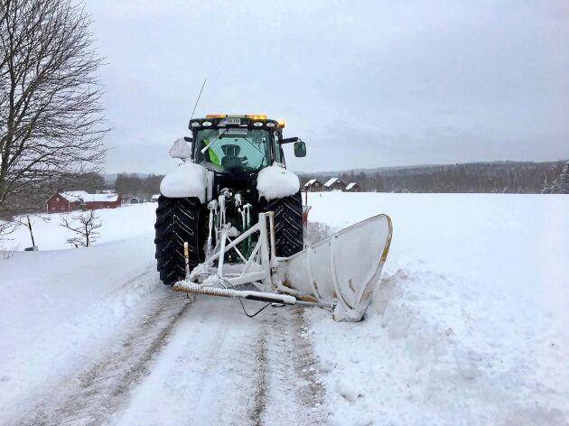 Det har fallit så mycket snö att Gustaf Norman får använda en vinge för att bryta ner vallar på sidorna av vägen. Sikten blir annars begränsad med höga vallar.