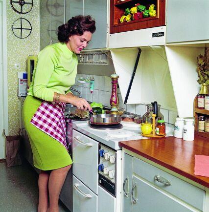 Rör om. Haide Göransson, mannekäng och fotomodell, lagar mat i ett typiskt 60-talskök. Notera – inga lådor bredvid spisen. Detta för att barn inte skulle kunna dra ut, klättra upp och sätta handen på plattan.