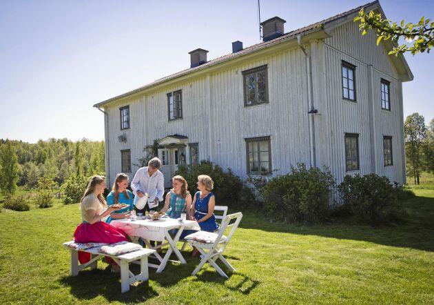 Pappa Lars-Inge serverar kaffe till sina döttrar och fru Ulrika utanför huset som byggdes i samma stil som