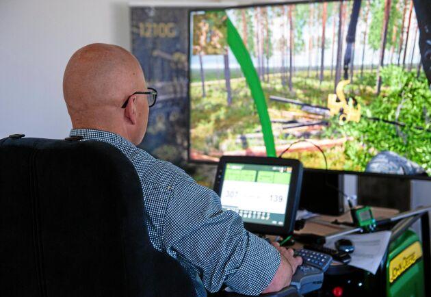 Här kör Thomas Åström skördare i en av John Deeres träningssimulatorer.