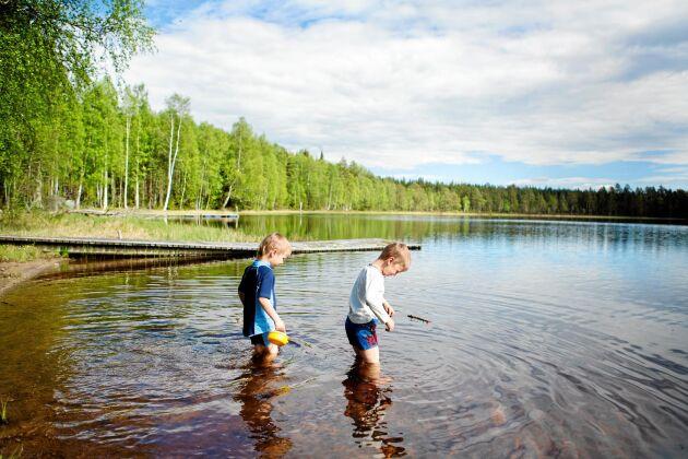 4-årige Sid och 5-årige Bo doppar fötter och ben i det än så länge ganska kyliga vattnet i sjön Grejsen.