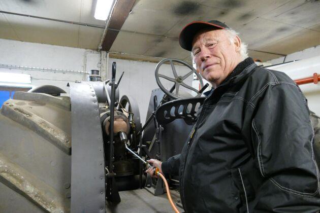 Lars-Åke Stuhre visar hur man värmer tändkulan med gasol på den 100 år gamla Munktelltraktorn.